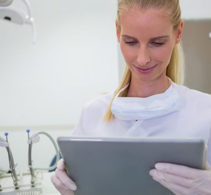 Female dentist using a digital tablet at clinic